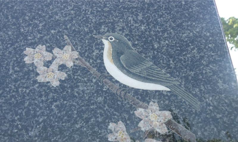 小鳥と桜の絵を象嵌装飾した墓石
